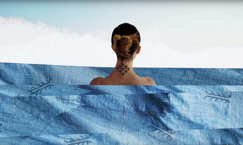 We're looking at a woman standing in the sea, her back to us, hair up showing the tattoo on her neck. The sea is a collage.