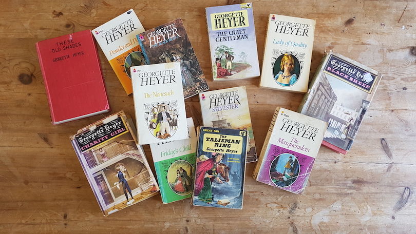 A dozen-ish romance books, all by Georgette Heyer, spread on a wooden surface.