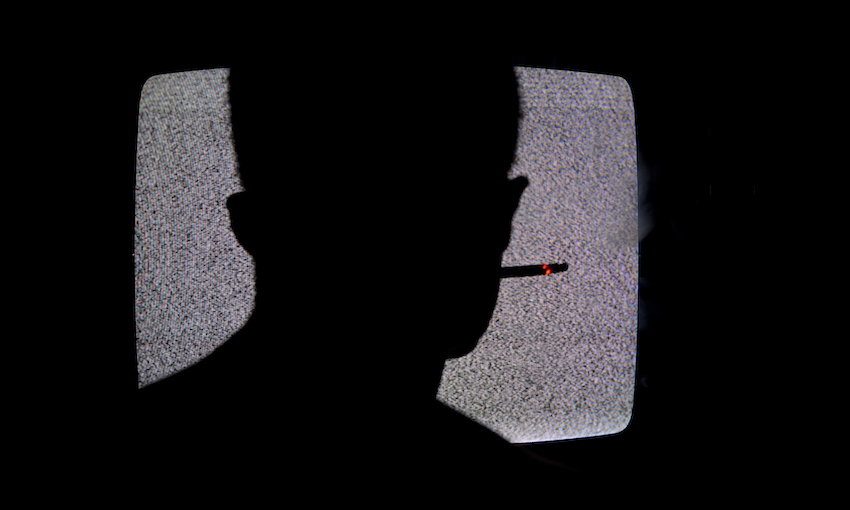 Silhouette Of Man Smoking Cigarette And Watching Television In Dark