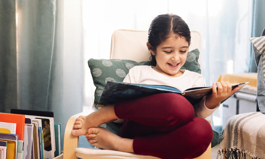 Photograph of a young girl curled up in a chair, barefoot, beaming as she reads a picture book.