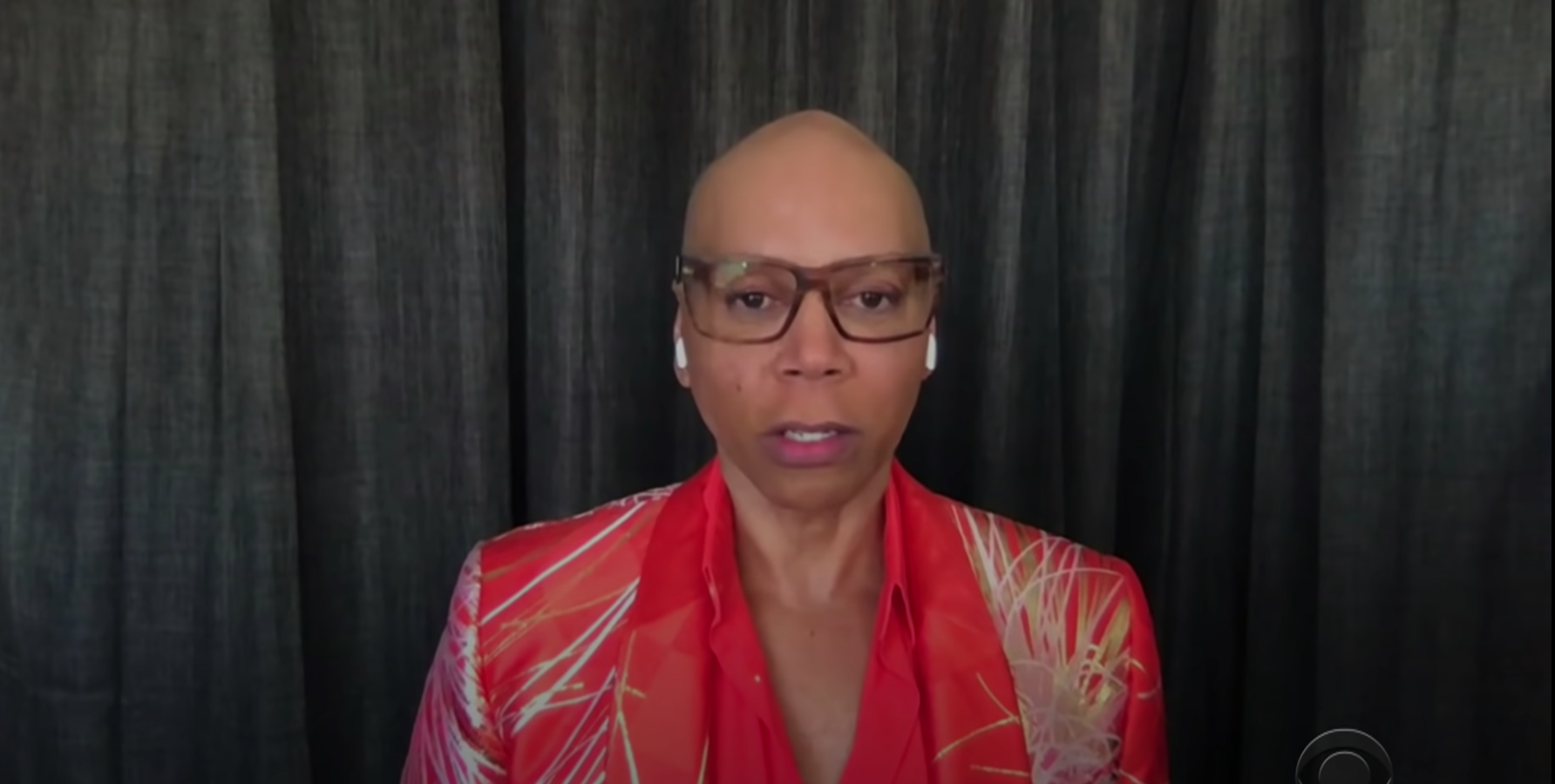 RuPaul in front of curtains