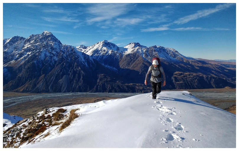 A beautiful clear day in the mountains, a young man trudging up a smooth stretch of snow towards camera.