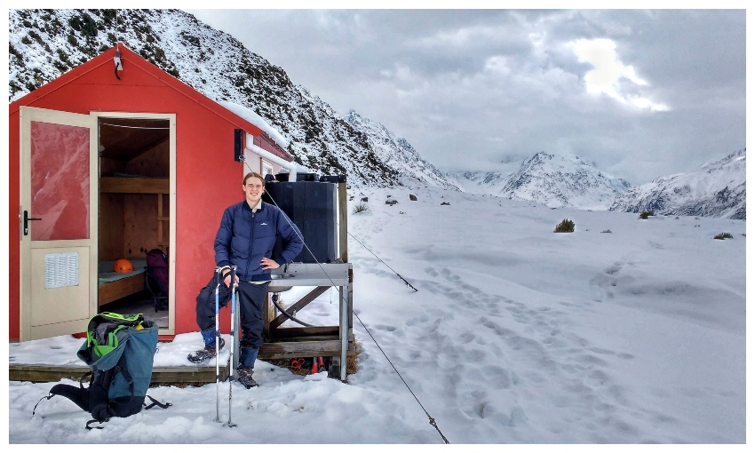 A young man in the snow, standing beside a bright red hut.