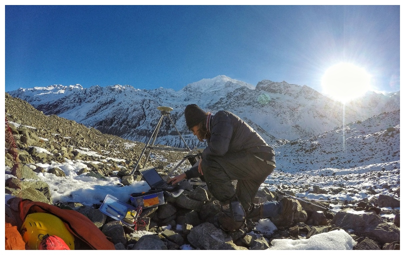 Young man adjusts scientific equipment in the bedrock of the Haupapa glacier. Beautiful clear day.