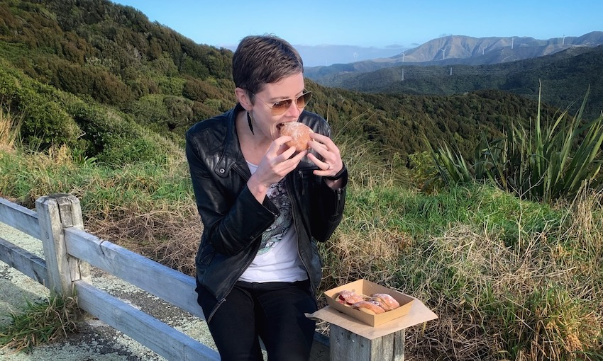 Woman sits on wooden fence biting into huge donut, box of donuts in front of her. Beautiful hills and sky in background.
