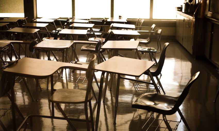 An empty classroom, desks and chairs, weird late afternoon light.
