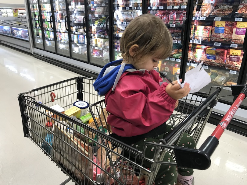 Toddler in trolley at supermarket, trolley loaded with pudding ingredients