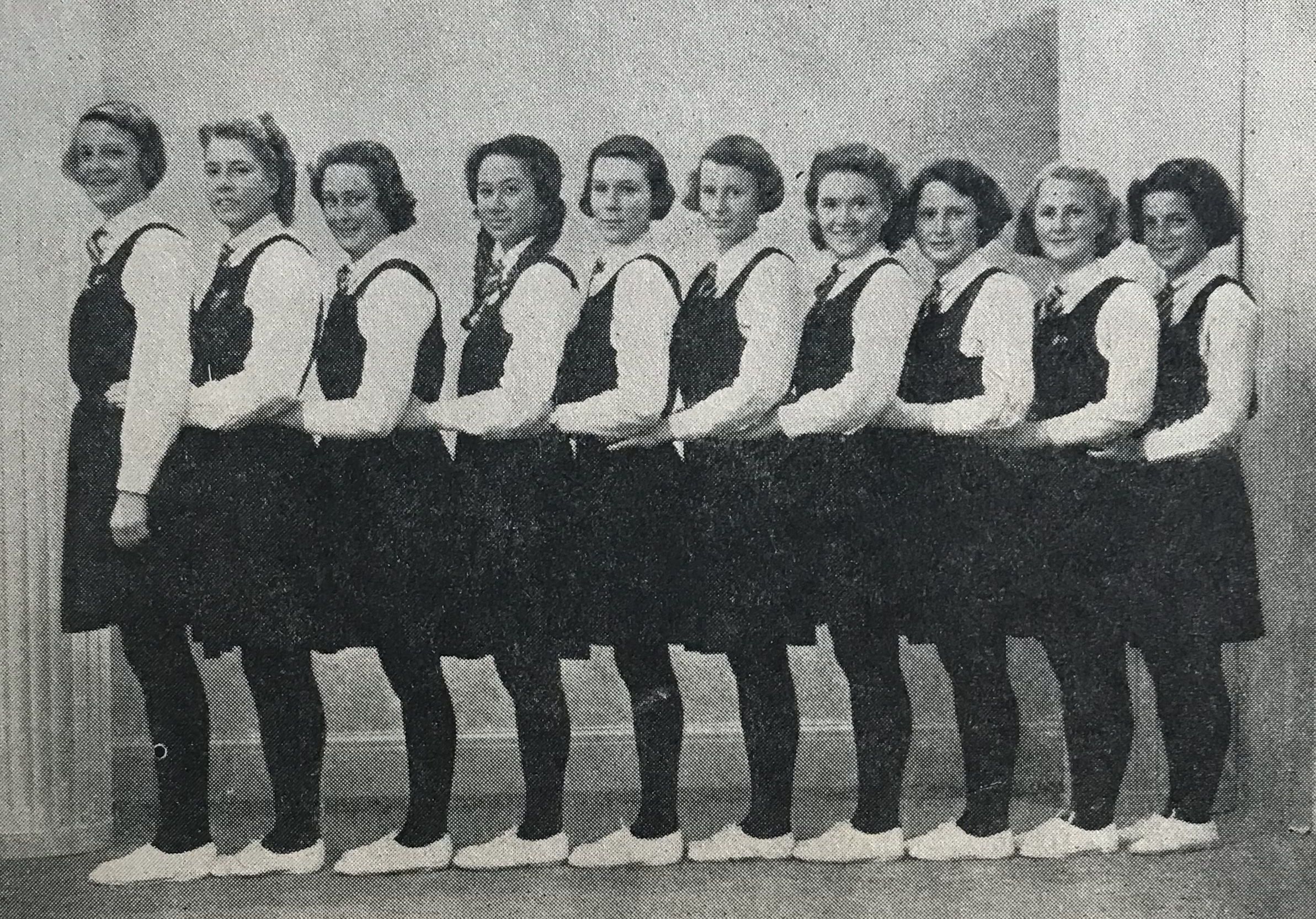 Black and white photograph of 10 schoolgirls in uniform, standing in a line with hands on the hips of the girl in front. One Māori girl, fourth from left.