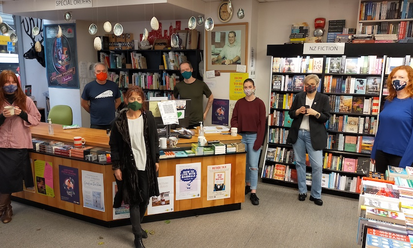 A bookstore, with seven masked staff standing facing camera