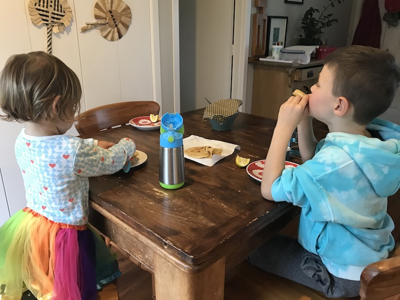 A kitchen table, two kids happily eating pancakes