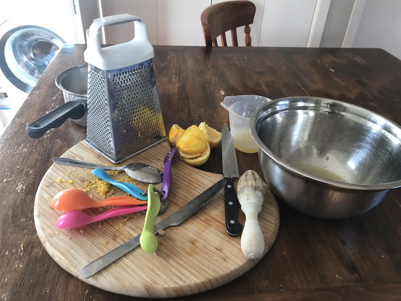 Cooking utensils and lemon skins on table