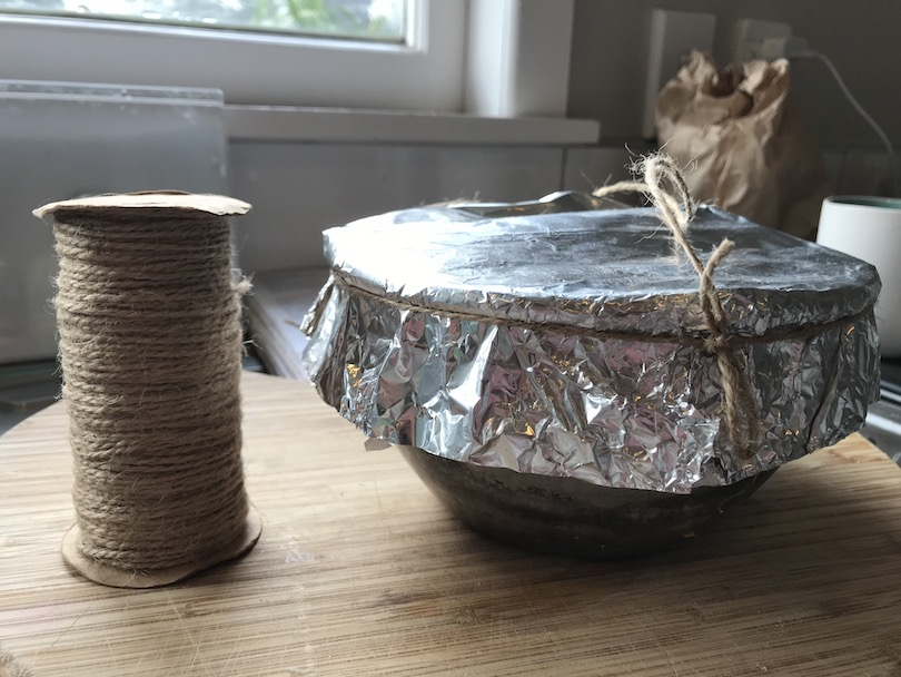 A reel of string and a bowl covered in tinfoil, on a chopping board