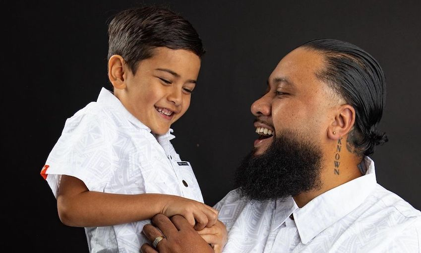 A father holds his son, both delighted, on his son's sixth birthday. Both wearing collared white shirts.