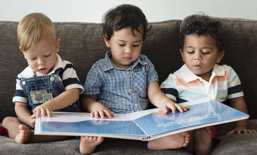 Three toddlers on a couch, reading one big picture book