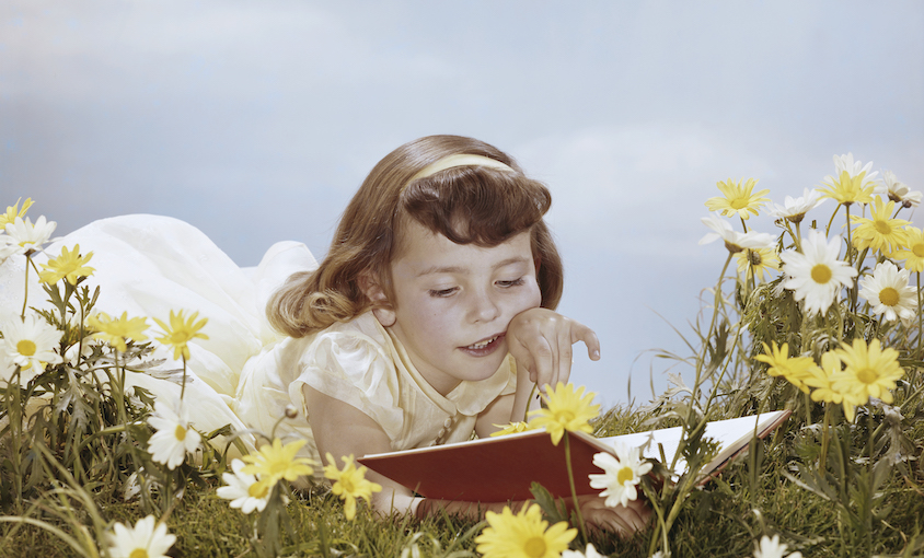 An old-timey photograph of a girl wearing a headband and lacey dress, lying in a dreamy meadow of daisies, reading a book. Bluebird sky.
