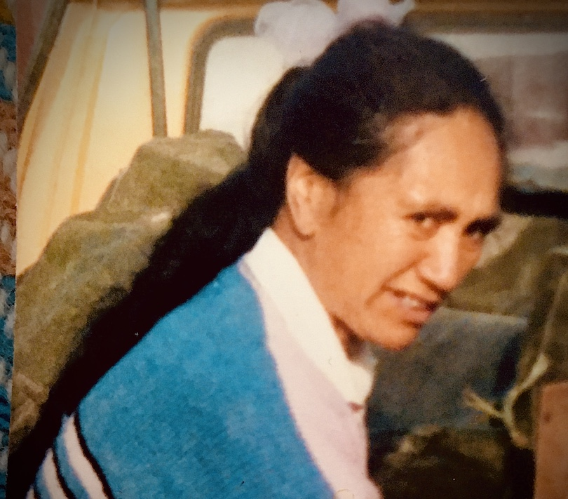 Old family photo of a middle-aged Māori woman, long hair in a ponytail, squinting and smiling at the camera.