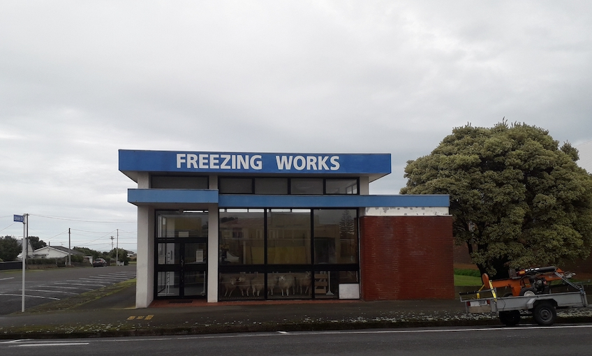 Photograph of a grey day in Pātea, view of an old building with FREEZING WORKS painted on the side