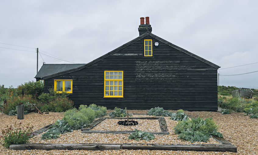 A photograph of a cottage, painted black with bright yellow window sills, in a striking garden of pebbles laid with sleepers and hardy plants.