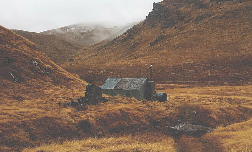 A landscape of rusty tussock, cold misty sky, a corrugated-iron hut at the base of a hill.