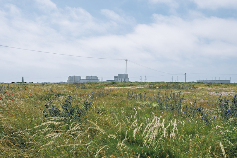 Photo of scrubby landscape, blue cloud-swept sky, looks cold. In the distance, a nuclear power plant.