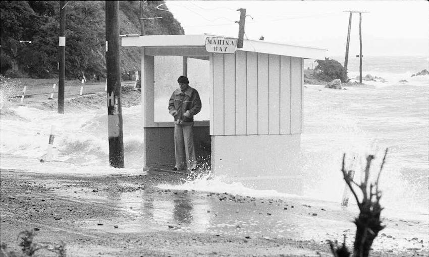 Old black and white image of a wild beach on Wellington's south coast, a man stands in a bus shelter beset by waves