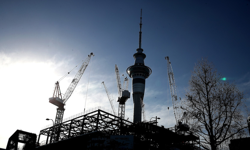 A clear day, the Skytower silhouetted, huge cranes rising up all around it, construction in the foreground