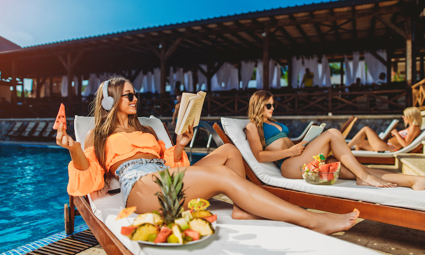 Beside a beautiful pool, on a beautiful day, three beautiful women are reading and eating beautiful fruits.
