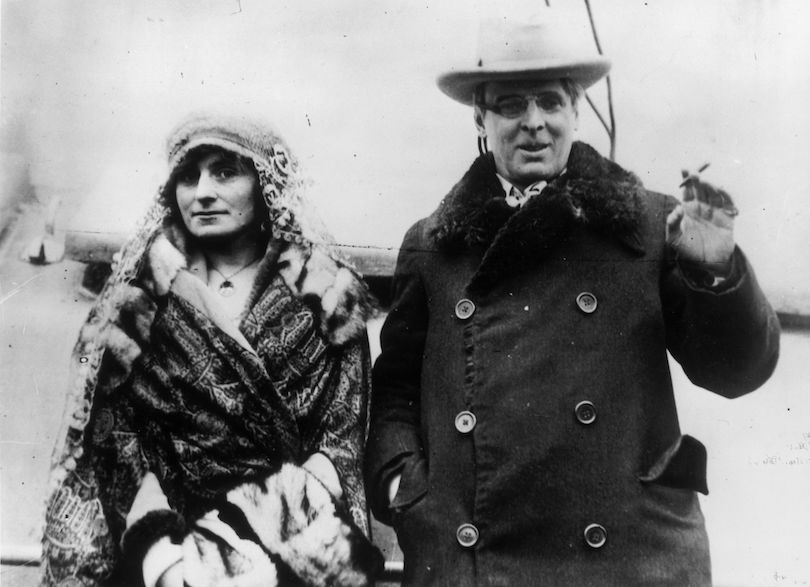 Old black and white photograph of a middle-aged couple walking toward camera, he is the centre of attention but she has a certain clever look in her eye