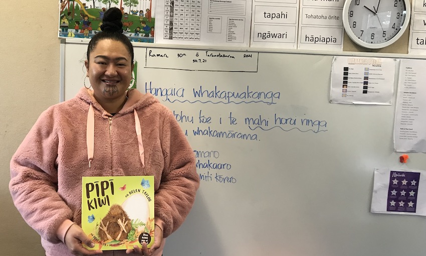 A Māori woman stands in front of a whiteboard, holding a picture book. Notes on whiteboard are in te reo. She's very proud of this space.