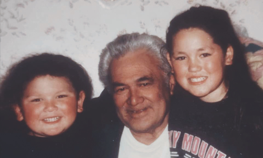 A family photo showing a grandfather flanked by two beaming kids, a boy and a girl.
