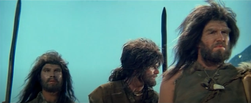 Still from an old film showing three actors dressed as Neanderthals. Terrible wigs.