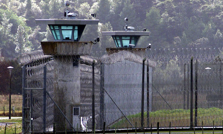 Exterior view of a prison yard and guard towers, backdrop of native bush