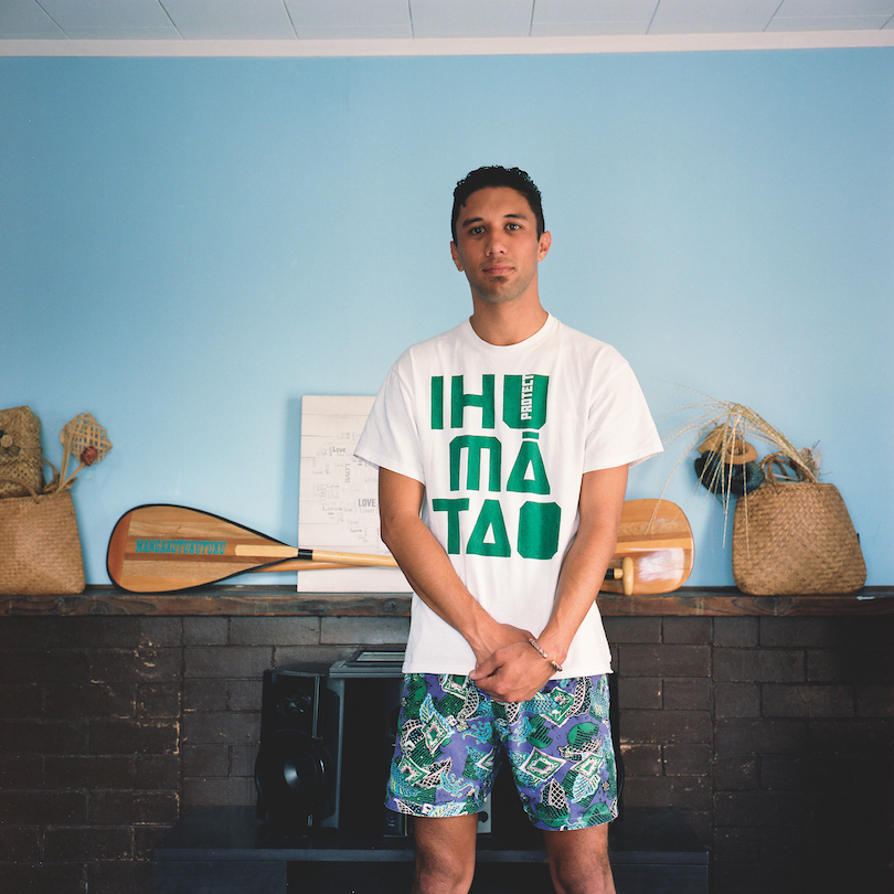 A young man wearing a Protect Ihumātao T shirt and boardies, stands in front of a mantelpiece display of kete and a waka paddle