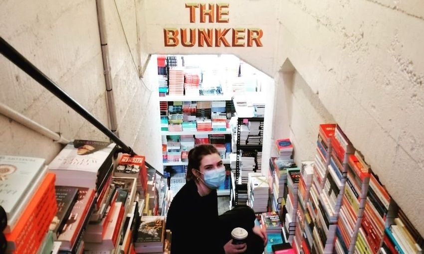 """A young woman holds a takeaway coffee and perches on the steps down to """"The Bunker"""", Unity's storage room, with glorious stacks of books all around."""