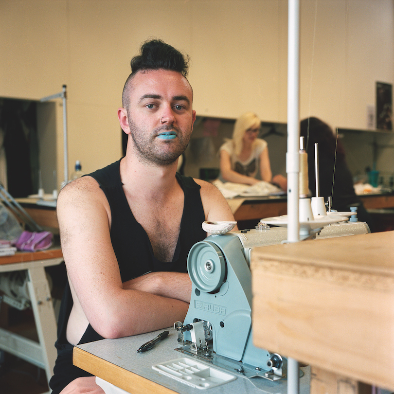 A young man wears a black singlet, blue lippy and a confident stare. He's seated at an industrial sewing machine, others (colleagues?) working in background.