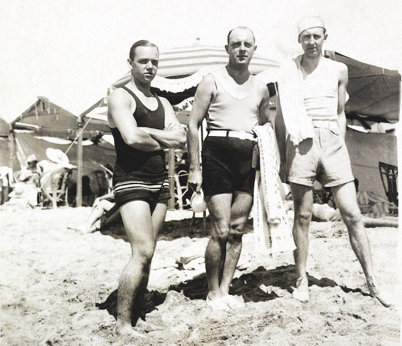 Black and white photo showing three men in front of what appear to be barracks. They're standing in sand.