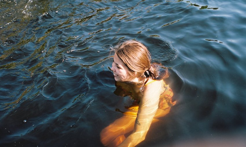 A young woman submerged in water up to her shoulders, dark water, outdoors, sun on her face, absolutely radiant