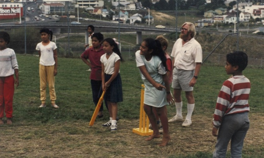 Photo of primary school kids playing cricket with those yellow plastic bat and wickets, a school playing field, a teacher in walk shorts