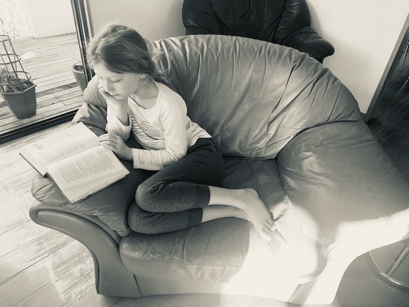 Black and white photo of a girl curled up reading in a patch of sunlight on a big cushy chair