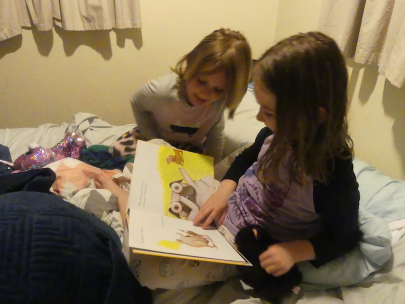 Two girls reading a picture book, sitting on a bed