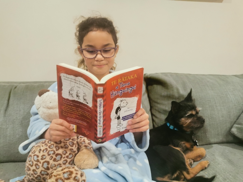 Young girl on a couch, a puppy beside her, she's wrapped up in a dressing gown and reading the te reo version of Diary of a Wimpy Kid.
