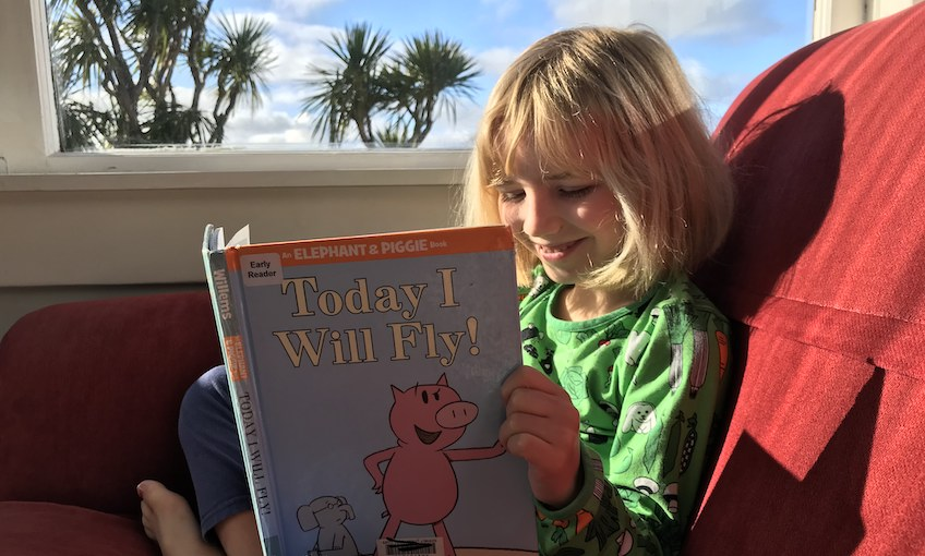 A blue-sky day, tī kōuka out the window, a blond, happy little girl sits on a bright red couch in the sun, reading.