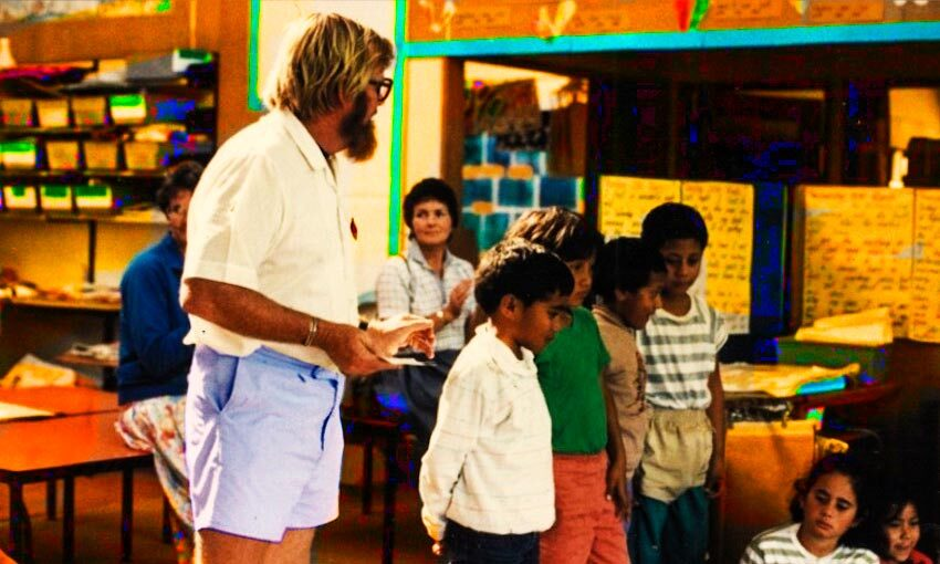 A 90s primary school classroom, male teacher with beard, short-sleeved shirt and walk shorts.