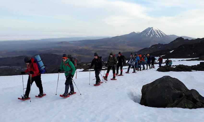 A trail of students hike through the snow, a snow-topped mountain can be seen in the background.