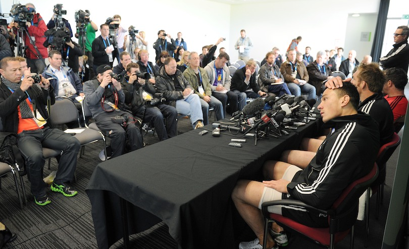 A sea of white male journalists, seated, face Sonny Bill Williams and a few other players (obscured) at a press conference. He looks uncomfortable, sitting awkwardly and scratching his head.