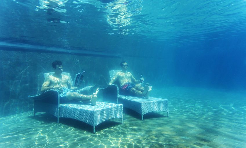 Two men on deckchairs at the bottom of a pool, one is reading, one gazing off into the distance.