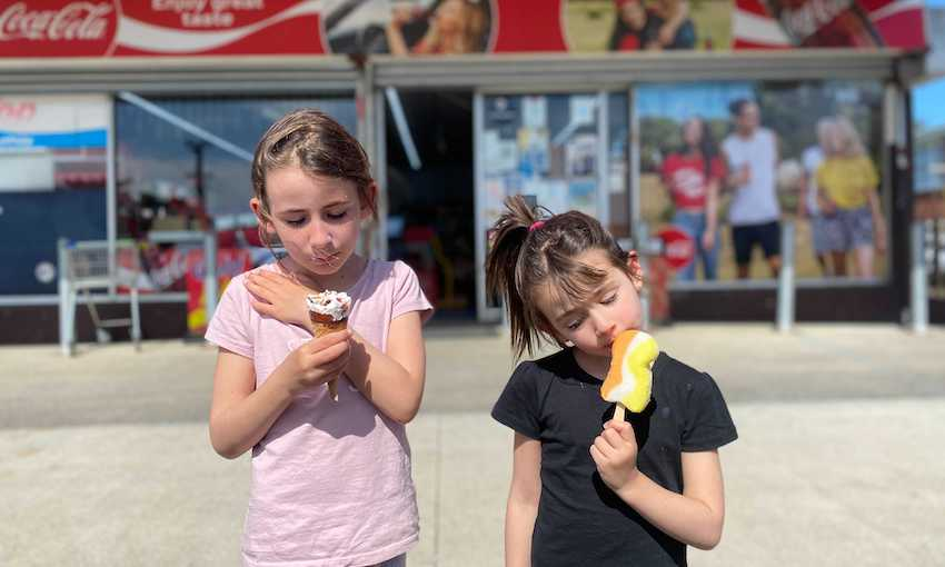 Two young girls lick iceblocks outside an Auckland dairy.
