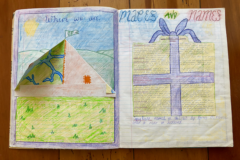A spread of an old school work book, showing beautifully coloured-in projects on Fiordland, including a pup tent with flaps that open.