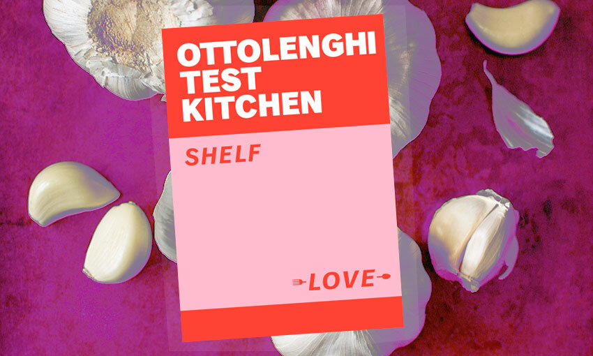 A purple background strewn with huge garlic cloves and full bulbs; on top a copy of Ottolenghi's Test Kitchen, a bright pink and red design triumph.